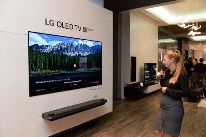 View of LG OLED TV AI ThinQ display zone, a female attendant tries out the TV's AI voice assistant features with the Magic Remote