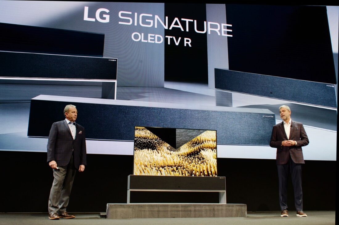David VanderWall, Senior Vice President of Marketing at LG Electronics USA and Tim Alessi Senior Director of Product Marketing for Home Entertainment Products at LG Electronics USA are onstage discussing the LG SIGNATURE OLED TV R at LG's CES 2019 Press Conference while putting the TV between them.