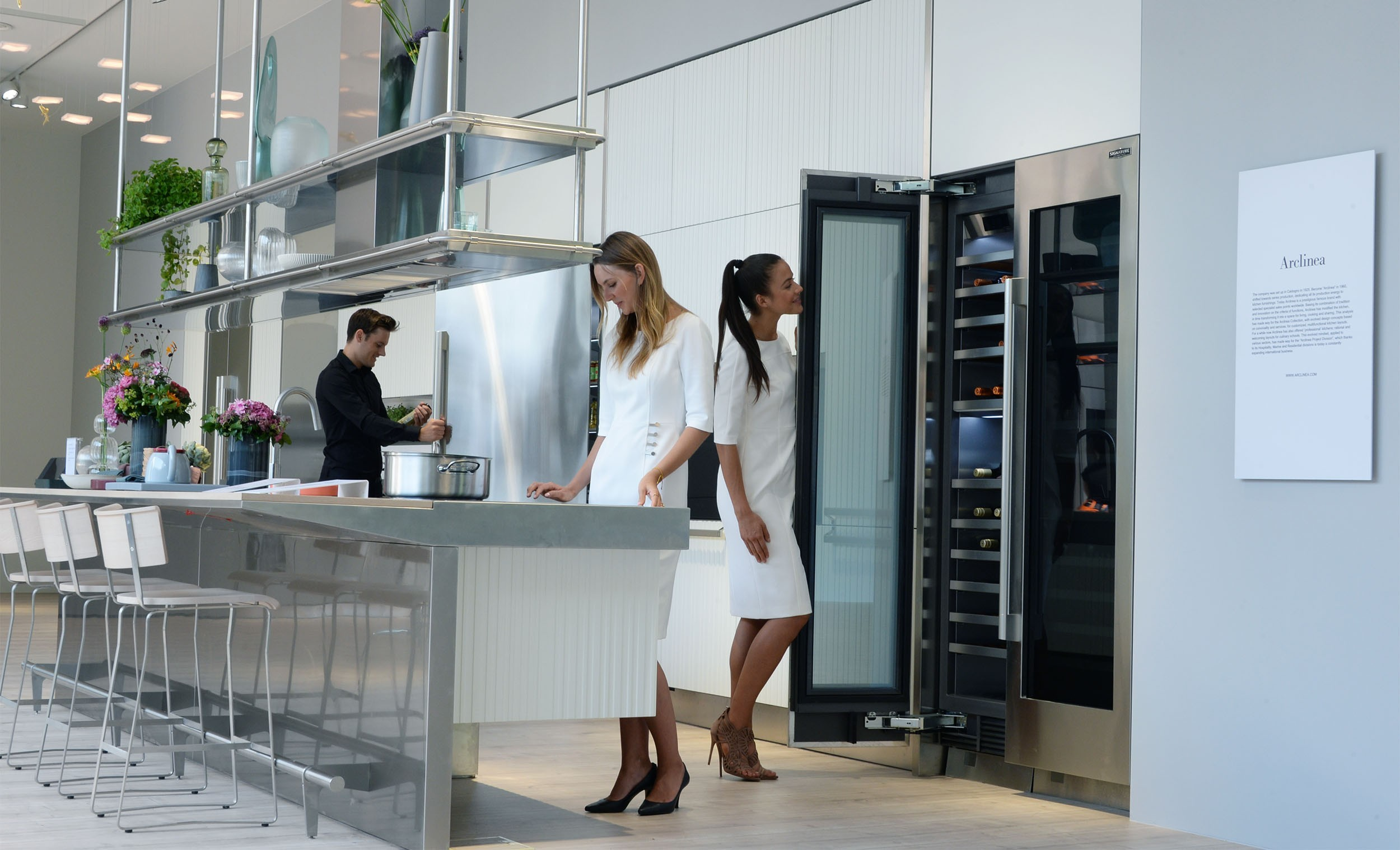 Another side view of the LG Signature Kitchen Suite display zone, three models are standing in the kitchen