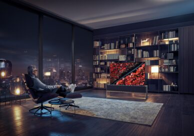 A man is relaxing in a chair at night, watching a nature scene on an LG SIGNATURE OLED TV R