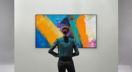 A woman admiring the LG GX Gallery series TV