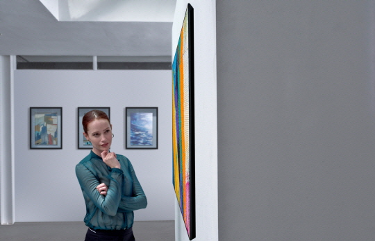 A side view of the LG GX Gallery series TV on display in a gallery with a woman looking at it with intrigue