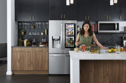 A woman preparing a beverage with Craft Ice™ in a kitchen with LG InstaView Door-in-Door™ refrigerator