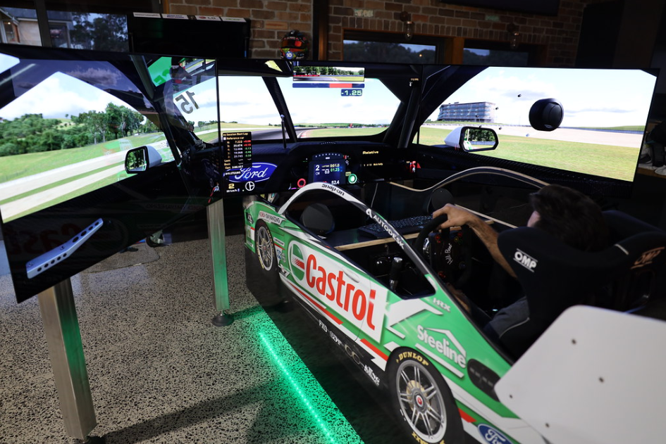 A complete view from the back of someone using the immersive racing simulator