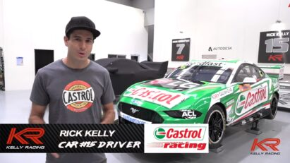 Racing driver Rick Kelly being interviewed in front of his green Ford Mustang GT