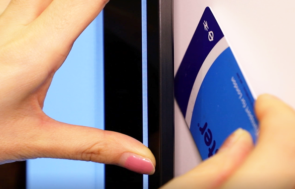 A woman uses her London transportation card to demonstrate just how thin the gap between the wall and the LG GX Gallery TV is