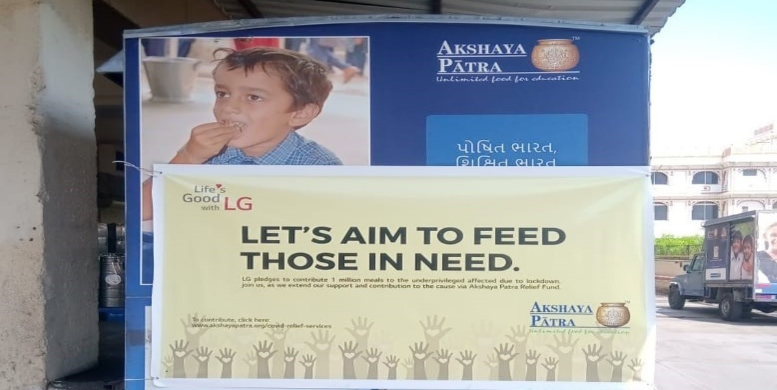 """The front shot of a banner reading """"Let's Aim to Feed those in Need"""""""