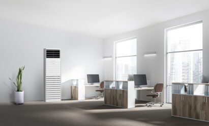 LG's commercial air purifier in an office with a flowerpot on the left and three office desks on the right