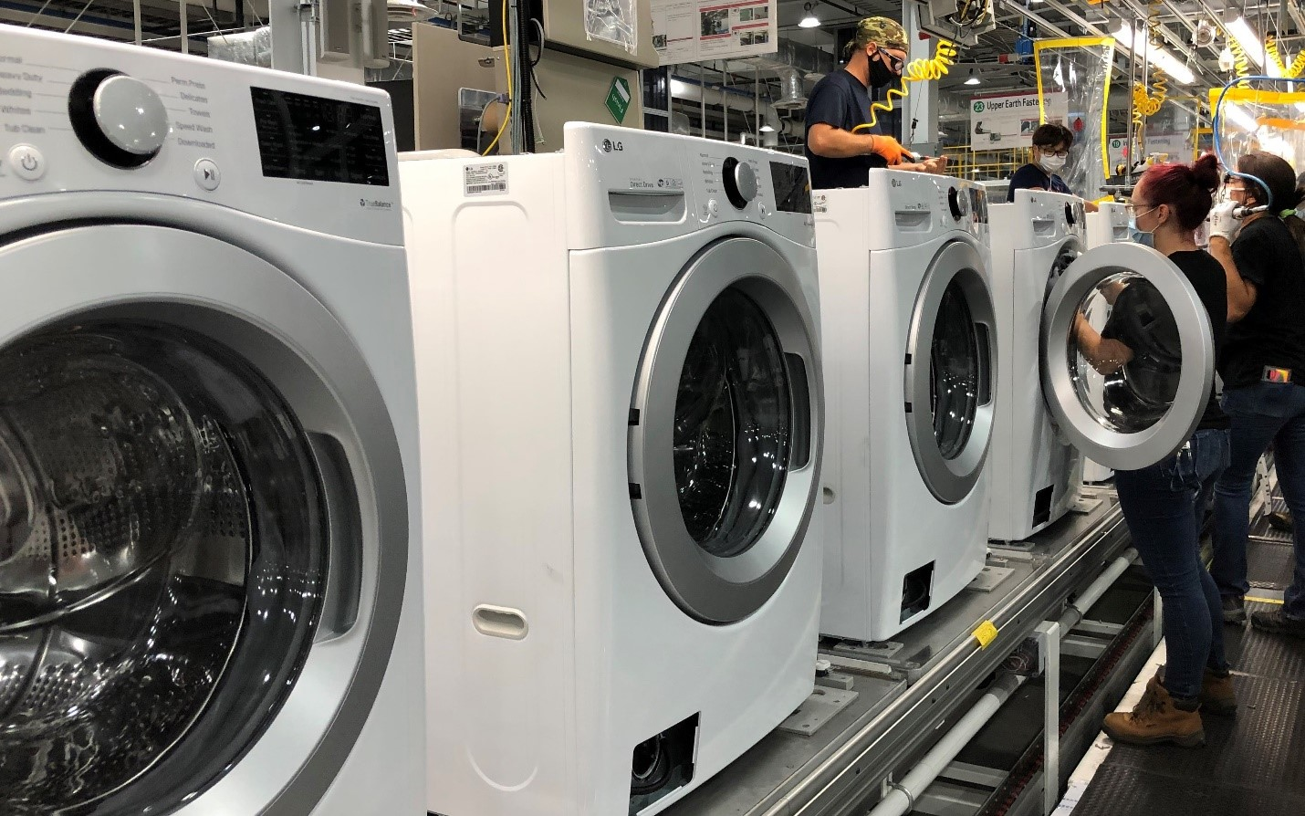 A team of US factory workers assembling LG washing machines moving down the production line