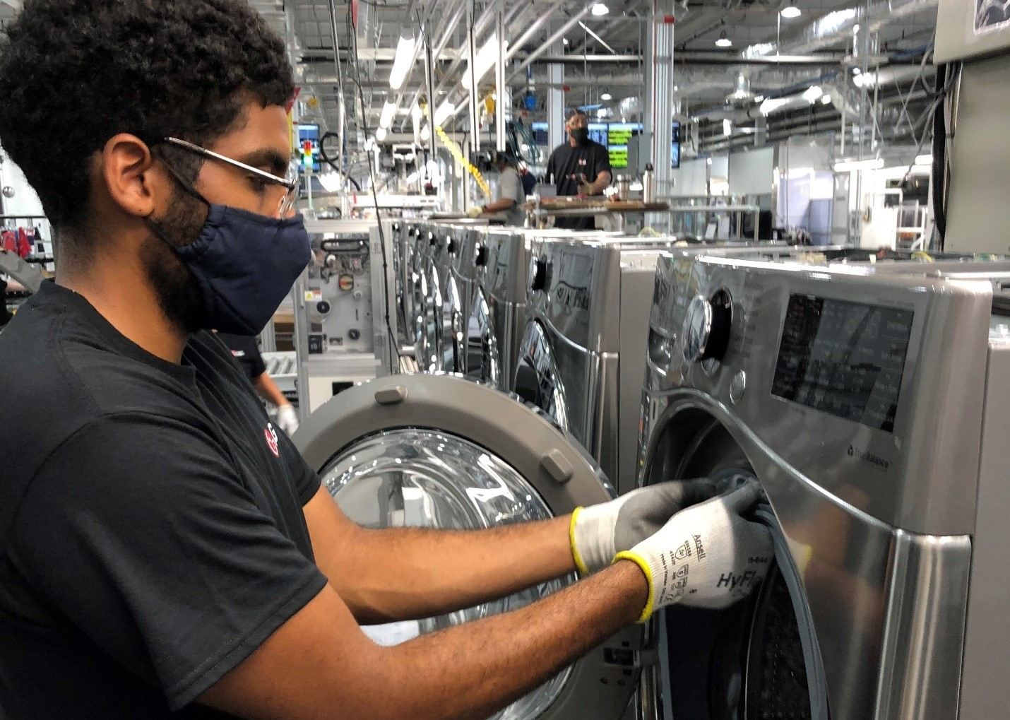 A closer look at one US factory worker fitting a part to the LG washer's door
