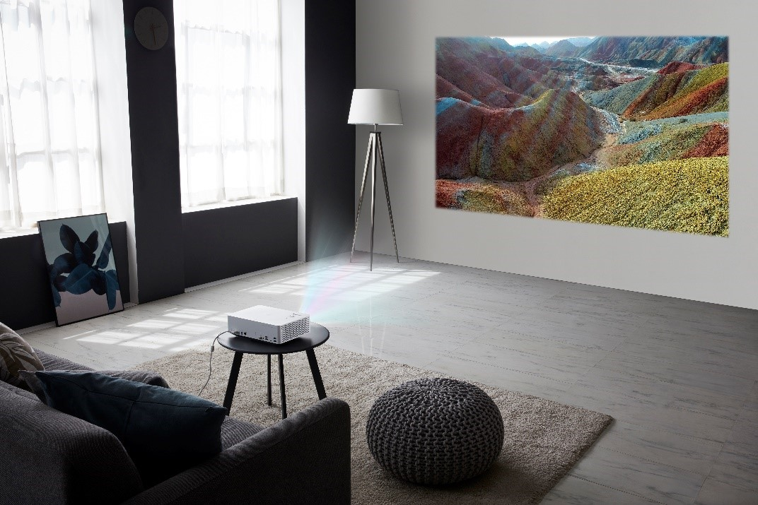 LG CineBeam stands on a small living room coffee table as it delivers vibrant images of a mountain forest in the room's bright conditions