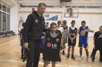 Participants of the LG Skills & Drills Contest watch on as one of the kids holds up an LG-branded jersey next to Greek basketball legend Thodoris Papaloukas