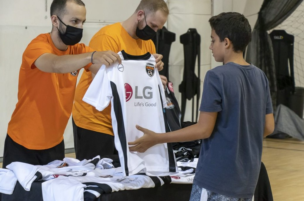 A member of staff giving out LG-sponsored uniforms to participants during the event