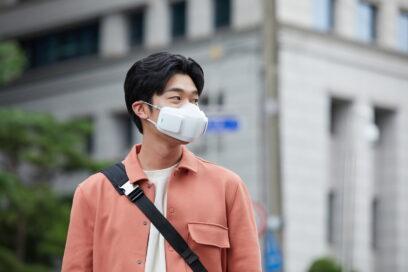 A man on a street wearing LG PuriCare™ wearable Air Purifier