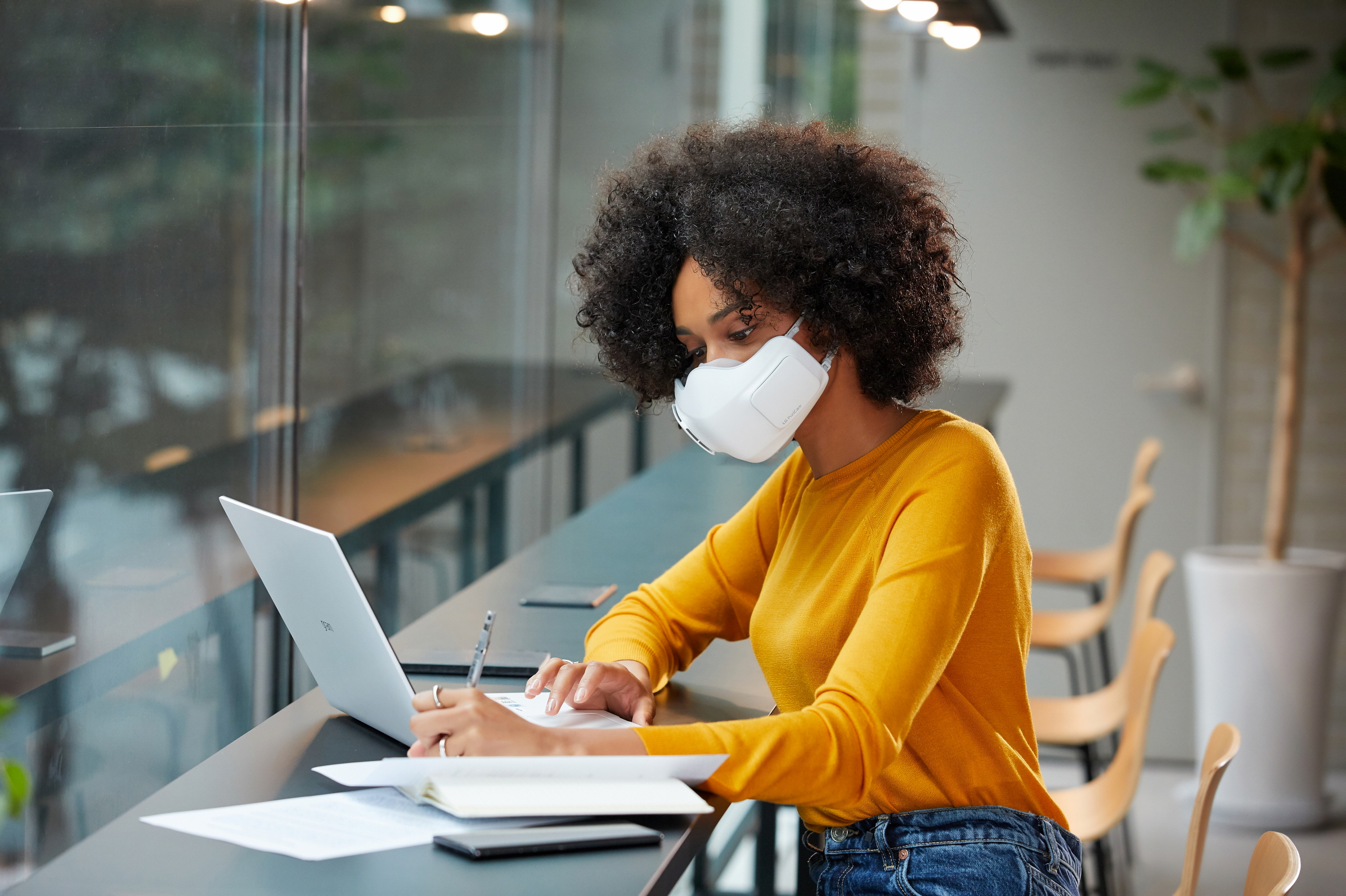 A woman wearing LG PuriCare™ wearable Air Purifier while working indoor