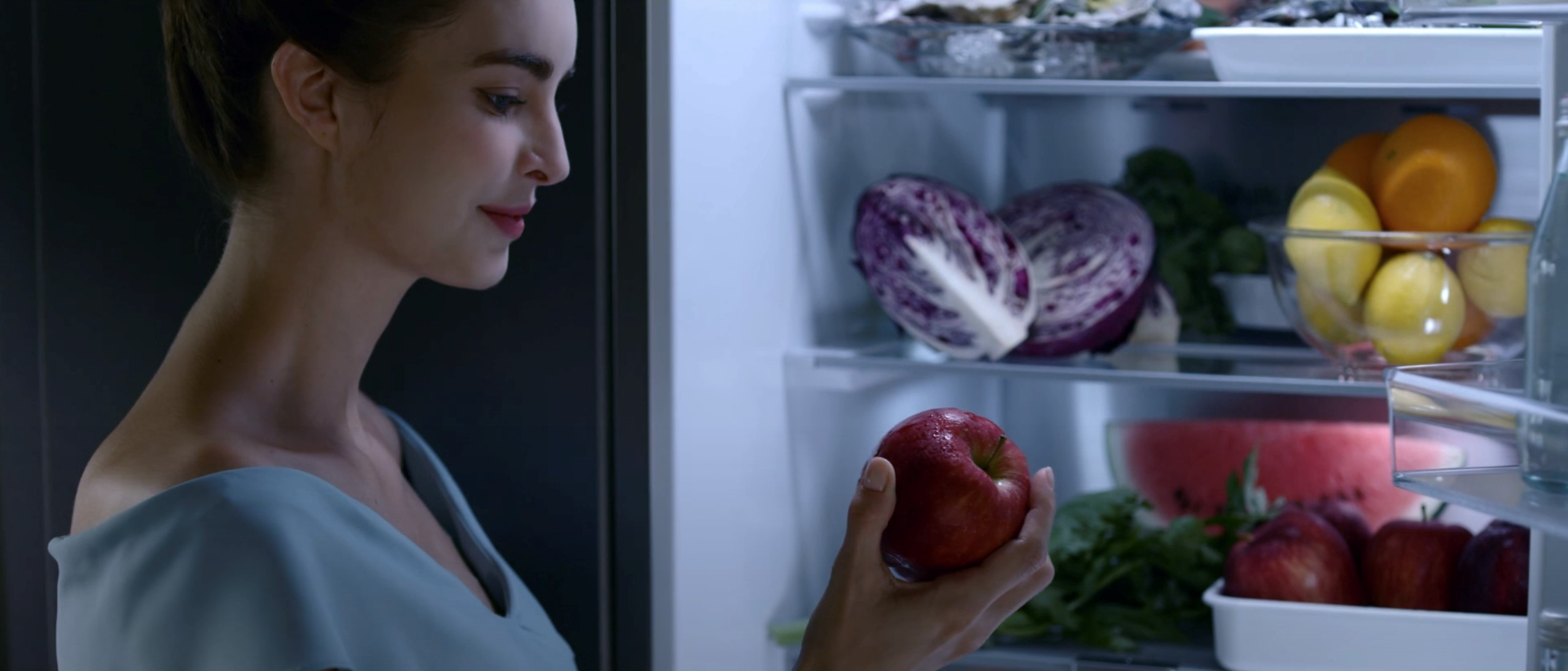 A woman takes an apple from her fruit and vegetable-filled LG refrigerator that keeps ingredients fresher for longer with HygieneFRESH+™ and LINEARCooling™ technology