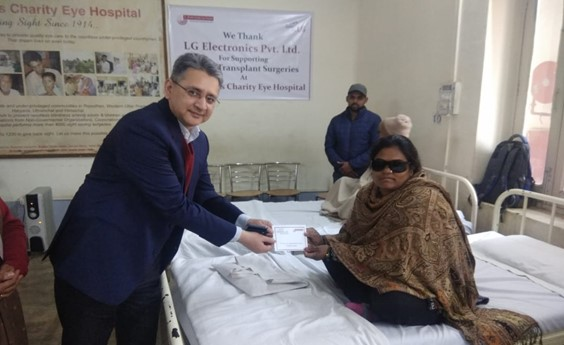 A man hands a patient a document at Dr. Shroff's Charity Eye Hospital