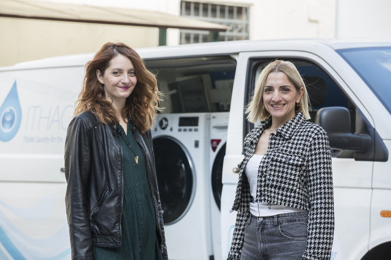 Dimitra Kountourioti, Ithaca's director of operations, and Georgia Stavropoulou, senior marketing manager at LG Greece, pose for a photo in front of Ithaca's mobile laundry van.