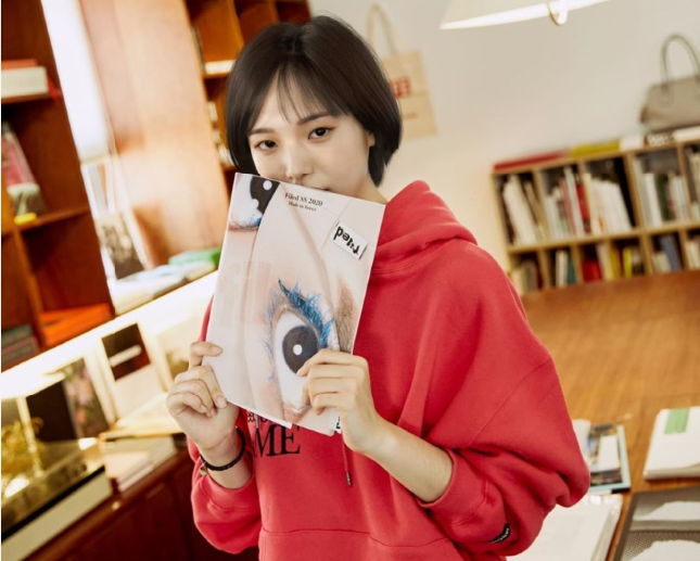 Reah Keem posing with a magazine.