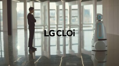 The LG CLOi robot designed to assist humans in public spaces standing face-to-face with a man in a building lobby.