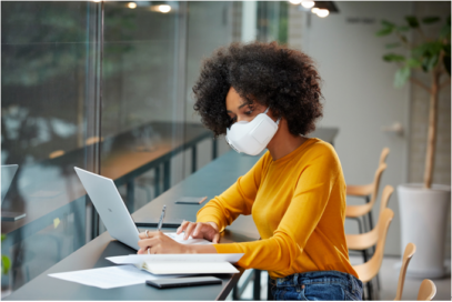 A woman wearing LG PuriCare™ Wearable Air Purifier as she works on a laptop at a cafe to protect herself during uncertain times.