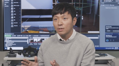 Ryu Byeong-gi, another featured digital designer at LG, explaining the role of a digital designer in front of his workspace equipped with a VR headset and large TV.