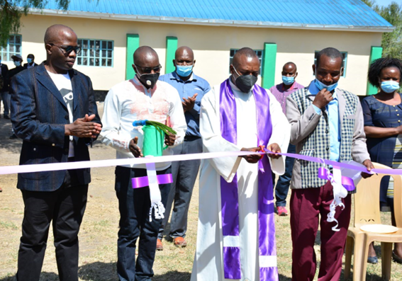 Father Joseph Mutuku cutting the ceremonial ribbon at the launch event of the project involving the construction of multiple facilities at Kyumbi Primary School in Machakos County.