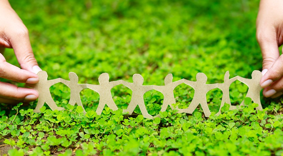 A person holding a paper chain family on a bed of grass.