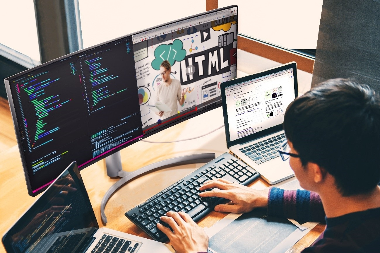 A computer programmer using the LG UltraWide Monitor with two laptops to multitask while working from home.