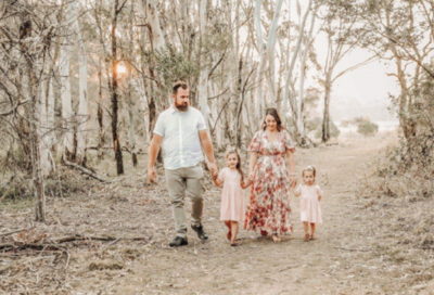 A family of four walking hand-in-hand through an Australian forest that has been ravaged by one of last year's bush fires.