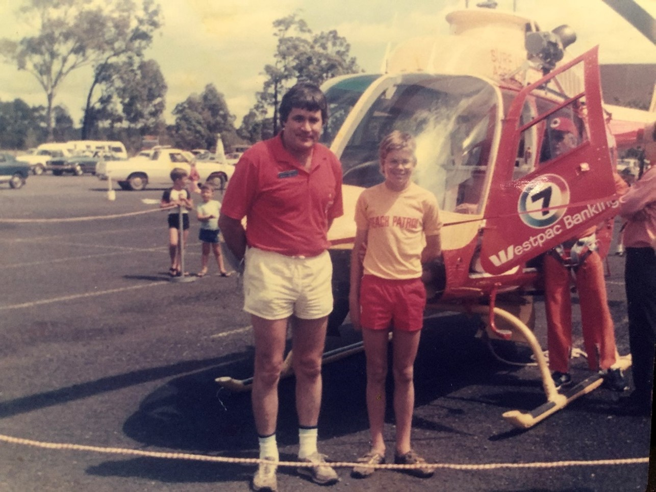 An old photo of Scott Collins and his father, who was also passionately involved in life-saving activities for over 40 years, posing in front of a helicopter.