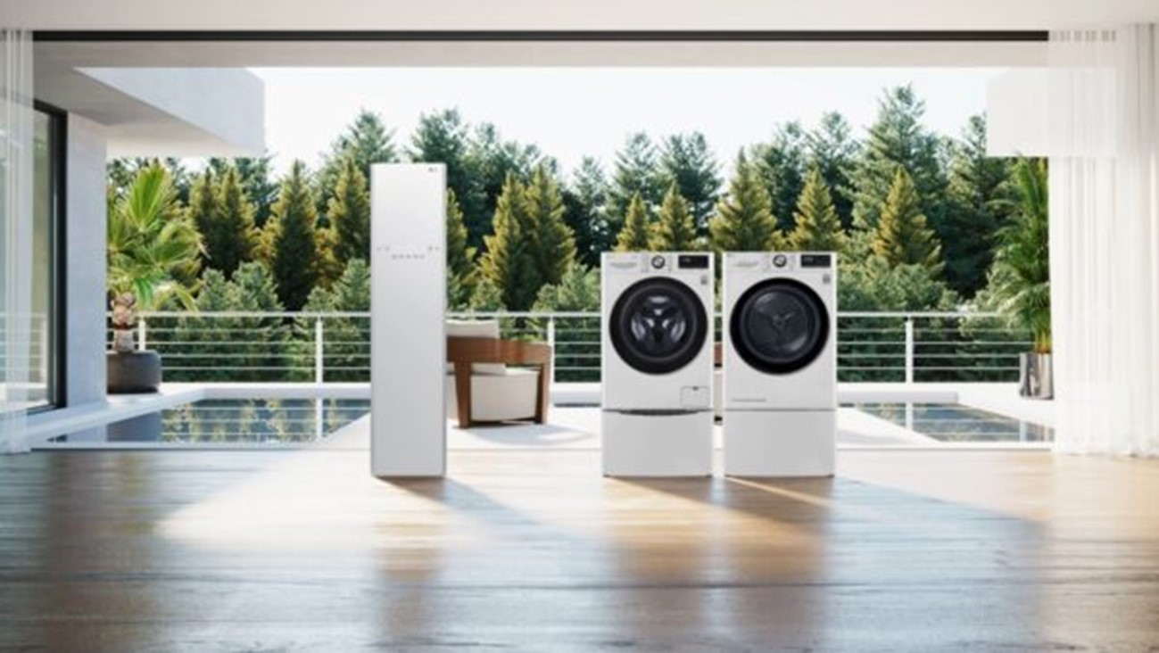 The white LG Styler and LG TWINWash being displayed in a spacious living room that overlooks a pool and a green forest.
