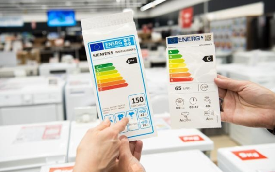 A close up of someone holding the new European Union energy labels now being displayed on green products