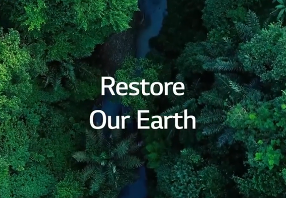 """A birds-eye view of a rainforest with a stream running through it and the phrase """"Restore Our Earth"""" overlapping."""